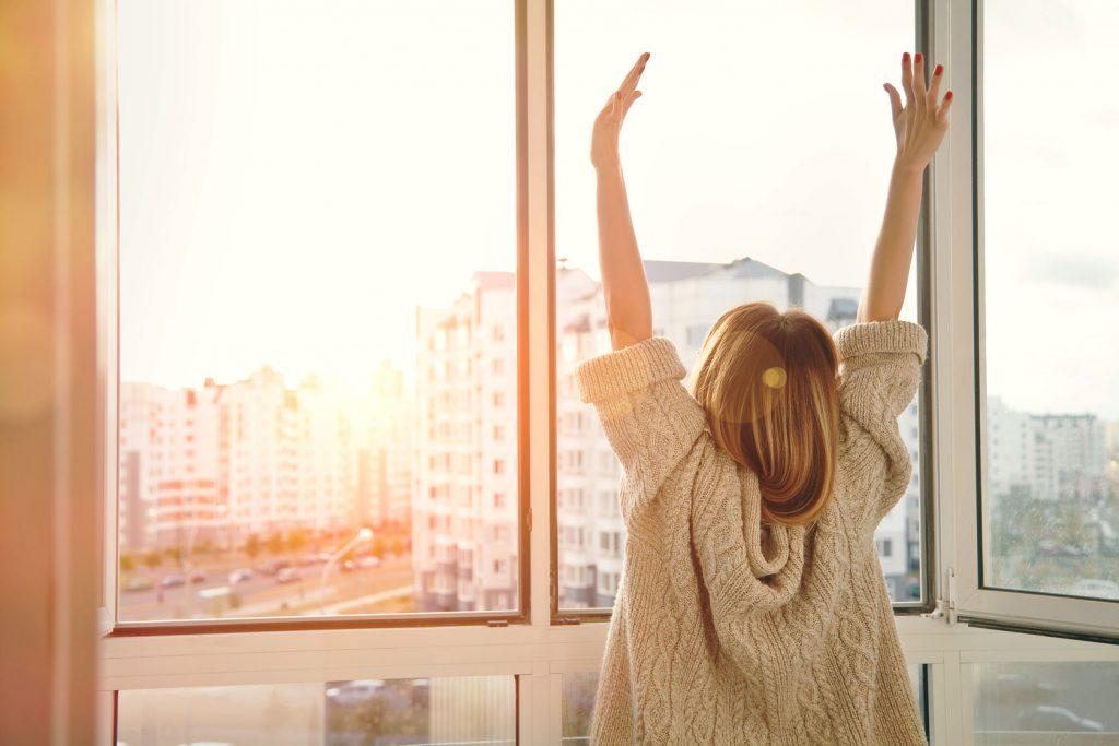 47462646 - woman near window raising hands facing the sunrise at morning